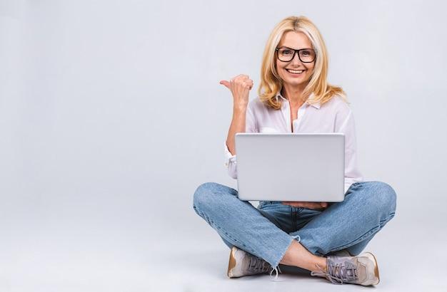 Conceito de negócios. retrato de mulher idosa sênior feliz casual sentado no chão em posição de lótus e segurando laptop isolado no fundo branco. copie o espaço para o texto.