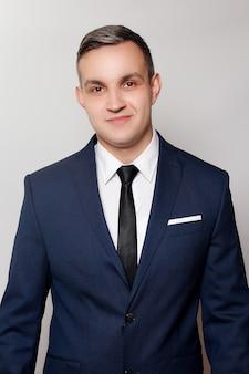Conceito de negócios, saúde, pessoas e estilo de vida - retrato de homem bonito em terno azul preto. fechar retrato de jovem feliz sorrindo alegre jovem