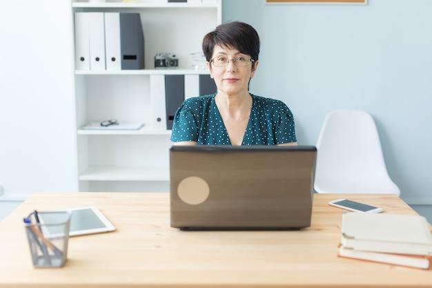 Conceito de negócios, tecnologia e pessoas - mulher de meia idade trabalha no escritório e usa um laptop.