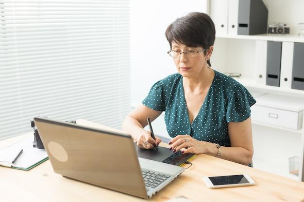Conceito de negócios, tecnologia e pessoas - mulher feliz usando mesa digitalizadora