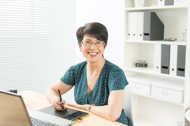 Conceito de negócios, tecnologia e pessoas - perto de uma mulher feliz usando a mesa digitalizadora.