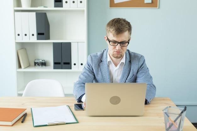Conceito de negócios, tecnologias e pessoas - homem bonito, trabalhando no escritório, no laptop.
