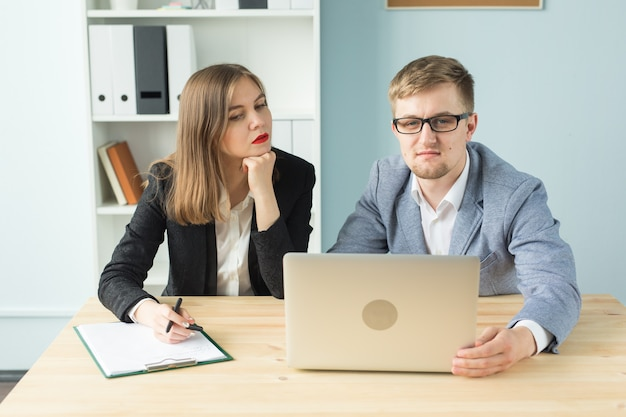 Conceito de negócios, trabalho em equipe e pessoas - dois colegas discutindo algum projeto interessante no escritório.