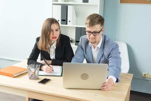 Conceito de negócios, trabalho em equipe e pessoas - homem sério e mulher atraente trabalhando em projeto no escritório