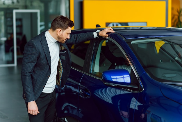 Conceito de negócios, venda de carros, consumismo e pessoas - homem feliz com salão de automóveis ou salão de beleza