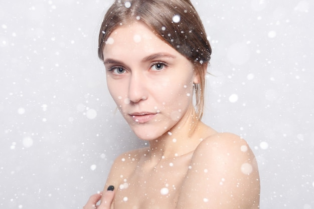 Conceito de neve, inverno, natal, beleza, cuidados com a pele e pessoas - mulher de spa. linda garota depois do banho, tocando seu rosto. senhora da beleza com uma toalha na cabeça tocando sua pele macia. sobre fundo de neve