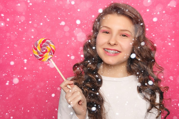 Conceito de neve, inverno, natal, dentes, emoções, saúde, pessoas, dentista e estilo de vida - mulher com aparelho dentário segurando pirulito. mulher de sorriso saudável com colchetes transparentes sobre fundo de neve