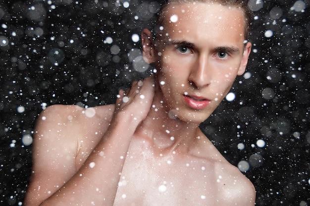 Conceito de neve, inverno, natal, pessoas, skincare e beleza - jovem molhado com cabelo preto em um fundo preto de neve. retrato masculino com peito raspado. cuidados com a pele dos homens. homem bonito musculoso e rasgado
