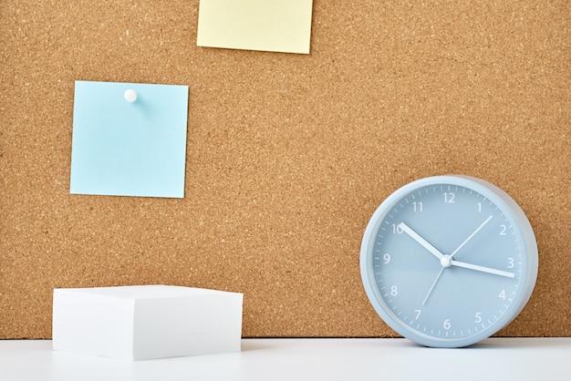 Conceito de notas, objetivos, memorando ou plano de ação. notas auto-adesivas em uma placa de cortiça e despertador no escritório no local de trabalho ou em casa