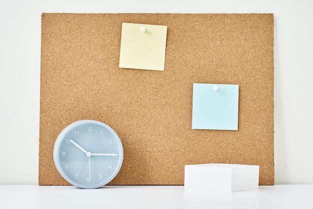 Conceito de notas, objetivos, memorando ou plano de ação. notas auto-adesivas em uma placa de cortiça e despertador no escritório ou em casa
