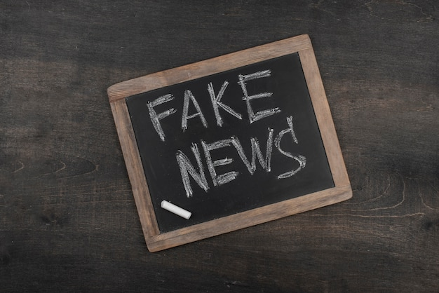 Conceito de notícias falsas com vista superior do quadro-negro