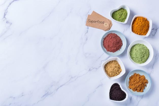 Conceito de nutrição equilibrada para uma dieta desintoxicante de antioxidantes de alimentação limpa. variedade de pó de superalimento - açaí, açafrão, trigo, gengibre, canela, matcha. camada plana, copie o fundo de mármore do espaço