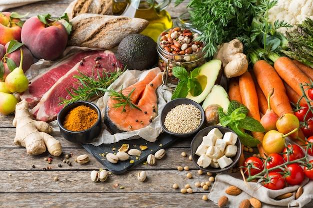 Conceito de nutrição equilibrada para uma dieta mediterrânea flexitariana de alimentação limpa. variedade de ingredientes de alimentos saudáveis para cozinhar em uma mesa de cozinha de madeira.