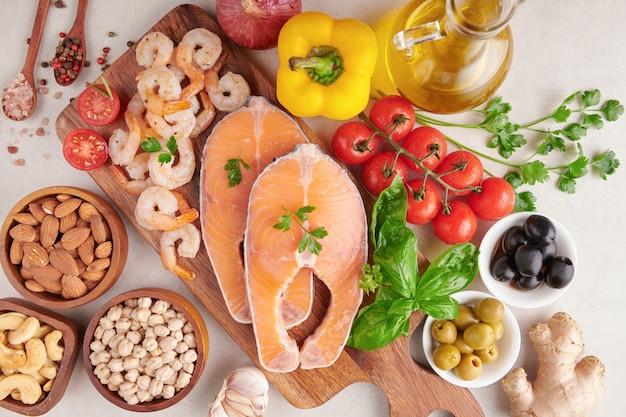 Conceito de nutrição equilibrada para uma dieta mediterrânea flexitariana de alimentação limpa vista superior plana. nutrição, conceito de comida de comer limpo. plano de dieta com vitaminas e minerais. salmão e camarão, misture vegetais