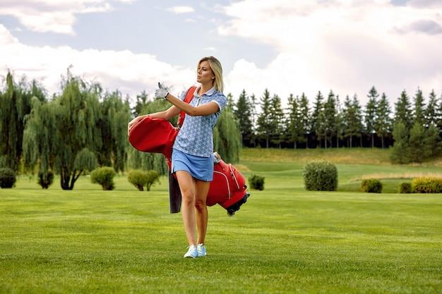 Conceito de objetivo, cópia espaço. mulheres que jogam o tempo que guarda o equipamento de golfe no campo verde. a busca da excelência, artesanato pessoal, esporte real, bandeira de esportes.
