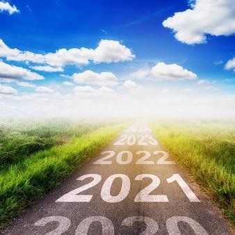 Conceito de objetivos de ano novo: pôr do sol vazio da estrada de asfalto e feliz ano novo 2021.