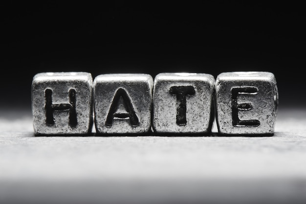 Conceito de ódio. inscrição 3d em cubos de metal em um fundo cinza preto isolado no estilo grunge