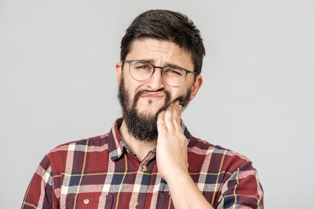 Conceito de odontologia e saúde. retrato de homem atraente incomodado, segurando a mão no dente