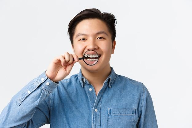 Conceito de ortodontia, atendimento odontológico e estomatologia. close de jovem asiático mostrando os dentes
