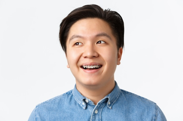 Conceito de ortodontia, atendimento odontológico e estomatologia. close-up de esperançoso, bonito homem asiático com aparelho dentário, olhando um sonho canto superior esquerdo, sorrindo satisfeito, fundo branco de pé.