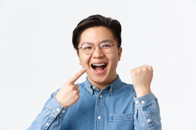 Conceito de ortodontia e estomatologia. close-up de homem asiático feliz satisfeito, apontando para o aparelho dentário e sorrindo amplamente, bomba de punho, regozijando-se, consertando os dentes, fundo branco de pé.