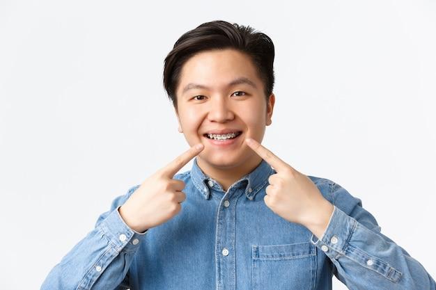 Conceito de ortodontia e estomatologia. close-up de um homem asiático sorridente e feliz, recomendando uma clínica odontológica, apontando o dedo para o aparelho dentário com uma expressão satisfeita, fundo branco