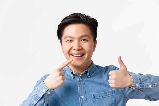 Conceito de ortodontia e estomatologia. recomendo close-up de um cara asiático satisfeito, cliente de clínica dentária sorrindo feliz e apontando para o aparelho dentário e mostrando os polegares para cima em aprovação.