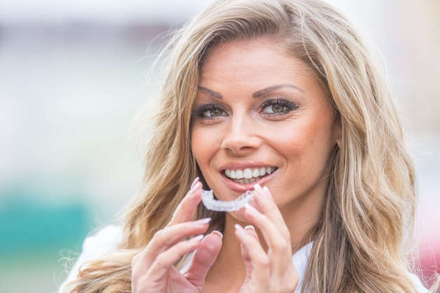 Conceito de ortodontia invisalign - jovem mulher atraente segurando - usando aparelho invisível ou treinador.