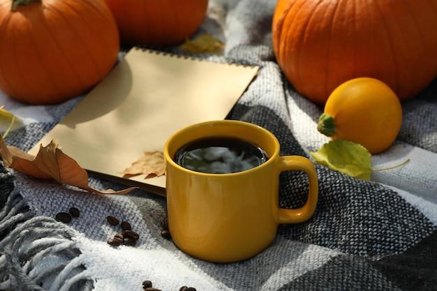 Conceito de outono aconchegante com abóboras e xícara de café ao ar livre