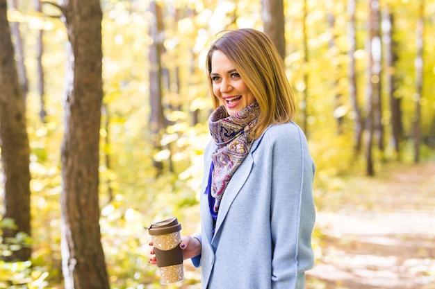 Conceito de outono, bebidas e pessoas - mulher segurando uma xícara de bebida quente