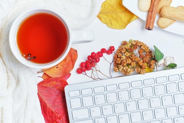 Conceito de outono com teclado em folhas secas com chá no suéter