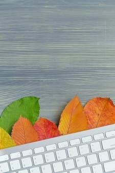 Conceito de outono com teclado em folhas secas com espaço de cópia
