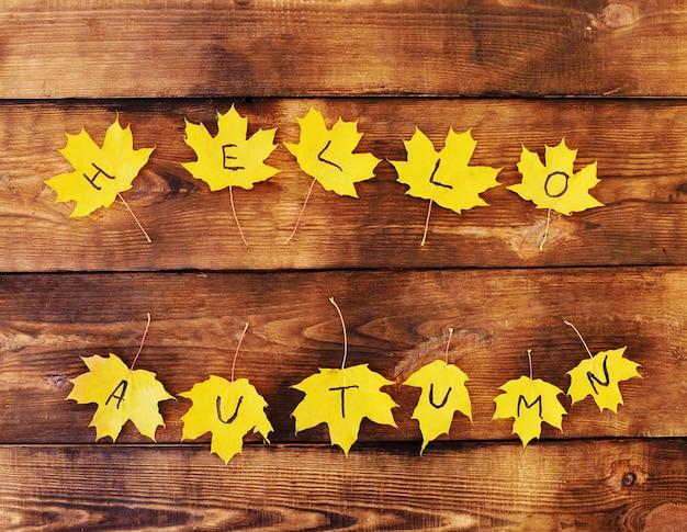 Conceito de outono - inscrição olá outono em folhas de plátano amarelas sobre um fundo de madeira.