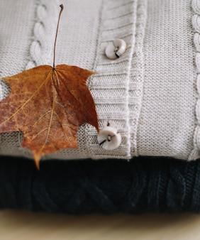 Conceito de outono inverno aconchegante com uma pilha de suéteres de malha e uma folha de bordo