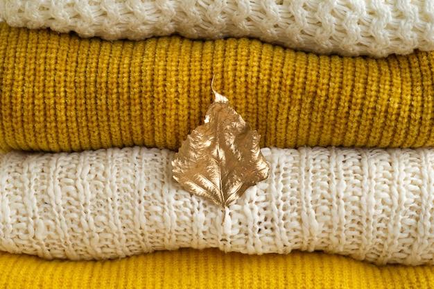 Conceito de outono-inverno. pilha de roupas de malha com folhas de outono ouro, fundo quente, malhas.