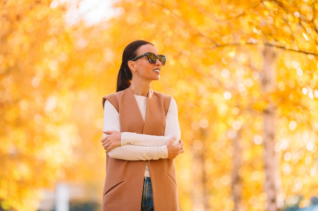 Conceito de outono - mulher bonita tomando café no parque outono sob folhagem de outono