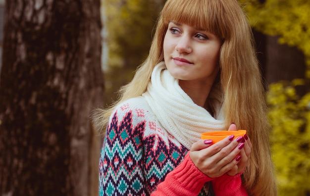 Conceito de outono - mulher de outono bebendo café no parque
