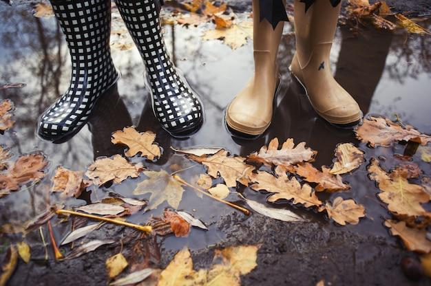 Conceito de outono outono com folhas coloridas e botas de chuva lá fora. feche de pés de mulheres andando com botas.