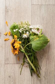 Conceito de outono. um buquê de flores murchas e um girassol no chão. postura plana