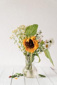 Conceito de outono. um buquê de flores secas murchas e um girassol em um vaso