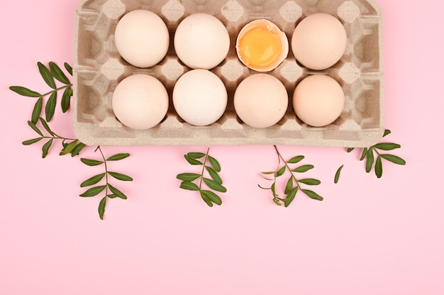 Conceito de ovos naturais. uma bandeja de ovos em um fundo branco e rosa. bandeja ecológica com testículos. tendência minimalista, vista superior. bandeja de ovos. conceito de páscoa