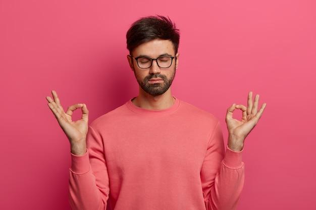 Conceito de paciência, calma e meditação. homem barbudo tranquilo e aliviado pratica exercícios de ioga, mantém as mãos em gestos zen, fecha os olhos, faz pose sobre uma parede rosa, controla suas emoções