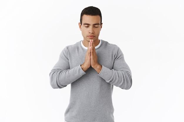 Conceito de paciência e meditação. calmo determinado jovem hispânico em suéter, orando a deus