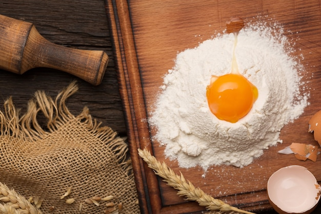 Conceito de padaria de cozimento de pão. ovos, farinha, espigas em uma mesa de madeira antiga.