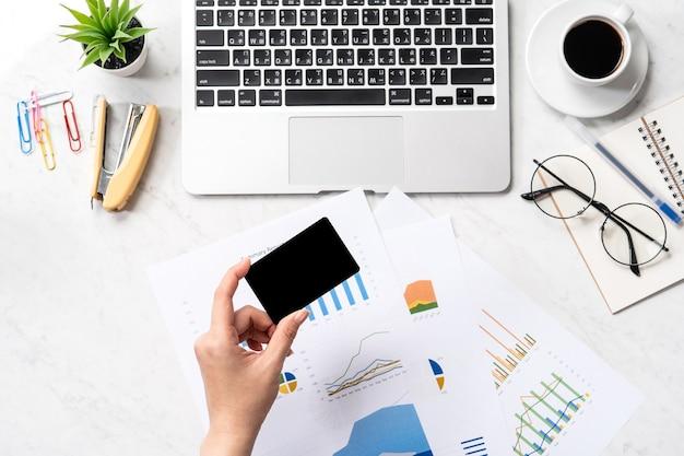 Conceito de pagamento de contas online, uma mulher usando mock up de cartão de crédito e celular na mesa do escritório isolado no fundo de mármore, cópia espaço, topview, flatlay, closeup
