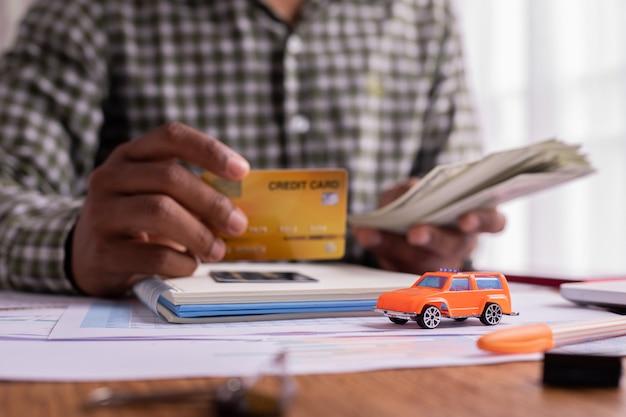 Conceito de pagamento em dinheiro, cartão de crédito para comprar, alugar um carro.