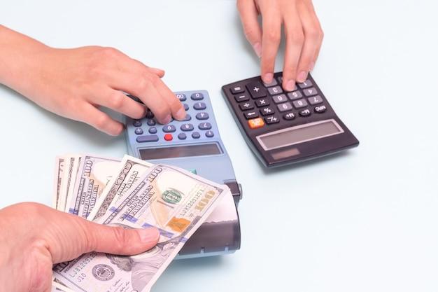 Conceito de pagamento em dinheiro. uma mão dando dinheiro para uma compra, uma mão pressionando botões em uma caixa registradora e calculando o custo em uma calculadora. cálculo e pagamento de impostos. conceito de black friday