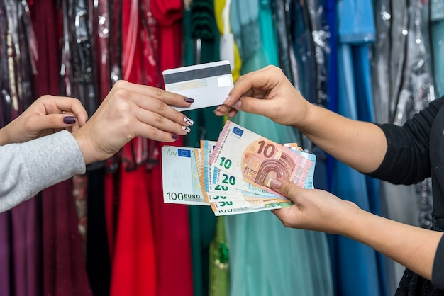 Conceito de pagamento. mãos femininas com euro e cartão de crédito