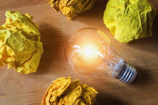 Conceito de papel amassado em torno da lâmpada na madeira para boa nova idéia
