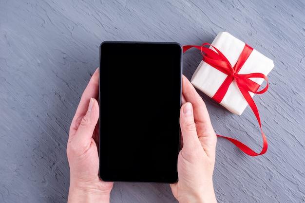 Conceito de parabéns online. as mãos seguram um tablet com uma tela preta em branco e um presente com uma fita vermelha em um fundo cinza